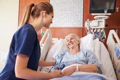 Sjuksköterska som talar till hög kvinnlig tålmodig i sjukhussäng arkivfoto