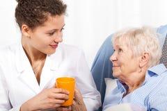 Sjuksköterska som tar omsorg av den äldre kvinnan Arkivbild