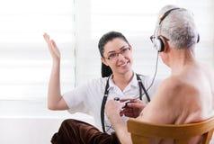 Sjuksköterska som tar omsorgod-gamala mannen Royaltyfri Foto