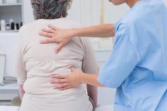 Sjuksköterska som tillbaka undersöker kvinnliga patienter i klinik Arkivbild