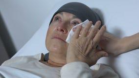 Sjuksköterska som torkar revor av den gamla kvinnan med cancer, rehabilitering efter kemoterapi stock video