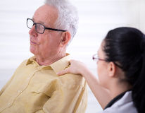 Sjuksköterska som tröstar den höga mannen Royaltyfri Fotografi