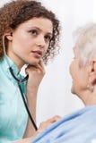 Sjuksköterska som undersöker den äldre damen arkivfoton