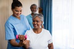 Sjuksköterska som vägleder den höga kvinnan i lyftande hantel royaltyfria bilder