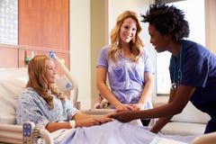 Sjuksköterska Talks To Mother med den tonårs- dottern i sjukhus royaltyfri bild