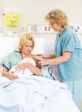 SjuksköterskaAssisting Woman In amning behandla som ett barn in arkivbilder