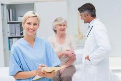 Sjuksköterskadanande anmäler medan doktorn och patienten som skakar händer Fotografering för Bildbyråer
