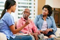 Sjuksköterskadanande noterar under hem- besök med pensionären kopplar ihop Arkivbild