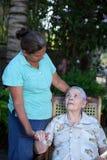 Sjuksköterskahjälp till den gamla damen Fotografering för Bildbyråer