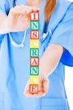 SjuksköterskaHolding Blocks Spelling ut försäkring över vita Backgroun Arkivfoton