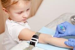 Sjuksköterskan desinficerar armen av lilla flickan, innan han utför en venipunc royaltyfri fotografi