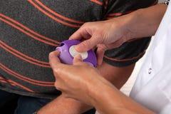 Sjuksköterskan ger anvisning hur man använder inhalatorn royaltyfri foto