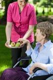 Sjuksköterskan ger en äldre kvinna päron Royaltyfri Foto