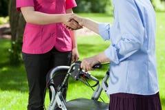 Sjuksköterskan ger handen det äldre en kvinna Arkivbild