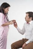 Sjuksköterskan ger pills till tålmodig arkivfoton