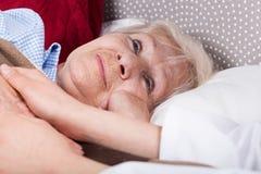 Sjuksköterskan ger service till den äldre kvinnan Arkivbild