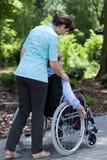 Sjuksköterskan gick ut för en gå med en äldre kvinna Royaltyfri Bild
