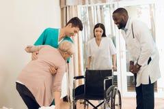 Sjuksköterskan hjälper en äldre kvinna att få ut ur säng och att få in i en rullstol Arkivbild