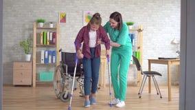 Sjuksköterskan hjälper en rörelsehindrad flicka att få upp från en rullstol efter en skada lager videofilmer