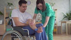 Sjuksköterskan hjälper i rehabiliteringen av en rörelsehindrad person i en rullstol stock video