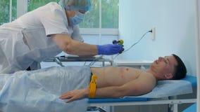 Sjuksköterskan i handskar och maskeringen som tar bort ECG, vadderar av den manliga patienten arkivfilmer