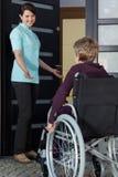 Sjuksköterskan inviterar en rörelsehindrad kvinna till huset fotografering för bildbyråer