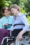 Sjuksköterskan kramar en äldre rörelsehindrad kvinna Royaltyfri Bild