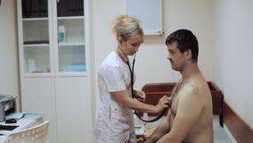 Sjuksköterskan lyssnar till en manlig patient via phonendoscope lager videofilmer