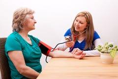 Sjuksköterskan mäter pensionären blodtrycket Arkivfoto