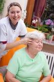Sjuksköterskan masserar huvudet av en pensionär Royaltyfri Fotografi