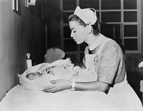 Sjuksköterskan med gråt behandla som ett barn Arkivbilder
