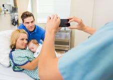 Sjuksköterskan nyfödda Photographing Couple With behandla som ett barn Royaltyfri Bild
