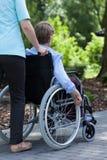 Sjuksköterskan skjuter rullstolen av en rörelsehindrad kvinna Royaltyfri Fotografi