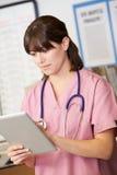 Sjuksköterskan som använder den Digital tableten på sjuksköterskor, posterar arkivbilder