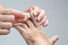 Sjuksköterskan som sätter bindemedel, förbinder på åldringhanden royaltyfria bilder