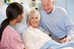 Sjuksköterskan som talar till pensionären, kopplar ihop avvärjer på Royaltyfria Bilder