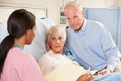 Sjuksköterskan som talar till pensionären, kopplar ihop avvärjer på Arkivfoto