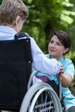 Sjuksköterskan stöttar det äldre en kvinna med ett handikapp royaltyfria bilder
