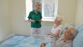 Sjuksköterskan talar med den manliga patienten och hans fru stock video