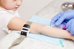 Sjuksköterskan tar en blodprövkopia från liten flickaarmen - pediatrisk ven arkivfoto
