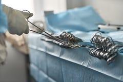 Sjuksköterskan tar kirurgisk tång royaltyfria foton