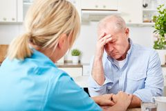 Sjuksköterskan tröstar den höga mannen med demens royaltyfria foton