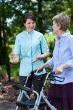 Sjuksköterskan uppmuntrar äldre kvinna för att gå Arkivbild