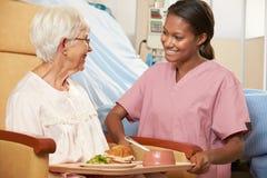 Sjuksköterskaportionmål till högt kvinnligt tålmodigt sammanträde i stol arkivbild