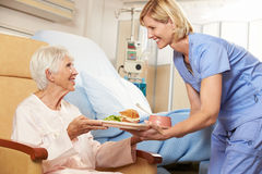 Sjuksköterskaportionmål till högt kvinnligt tålmodigt sammanträde i stol arkivfoton