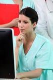 Sjuksköterskasammanträde på hennes skrivbord Royaltyfria Bilder