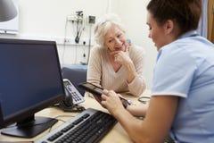 SjuksköterskaShowing Patient Test resultat på den Digital minnestavlan royaltyfri foto