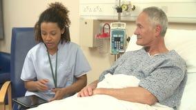 SjuksköterskaSitting By Male patients säng genom att använda den Digital minnestavlan stock video