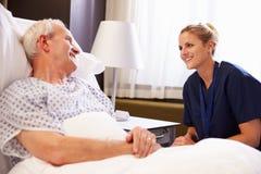 SjuksköterskaTalking To Senior manlig patient i sjukhussäng royaltyfria foton