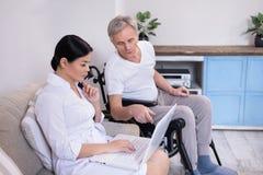 Sjuksköterskavisning något till patienten via bärbara datorn arkivfoto